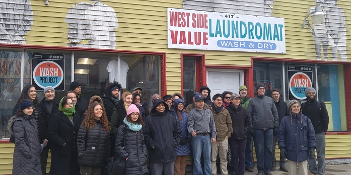 NEC staff and volunteer coordinators in winter gear posing outside the WASH Project, a bright yellow building